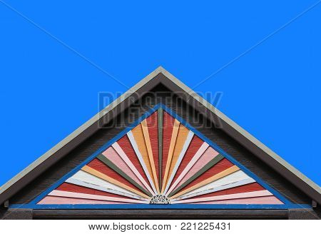 old color wood panels house wall gable roof and clear blue sky