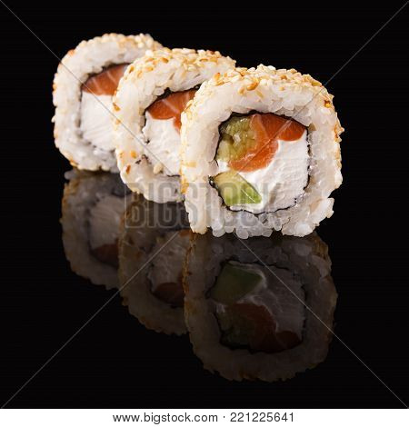 Set of three sushi rolls with fish, vegetables and cheese. Traditional japanese food on black glass with reflection, copy space. Asian restaurant meals delivery
