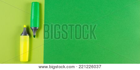 Two marker highlighter pens on green background