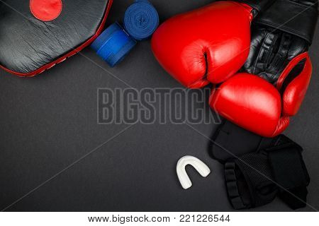 Pairs of red leather boxing gloves and blue hand wraps, inner gloves on black surface