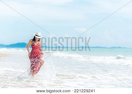 Summer Day.  Smiling woman wearing fashion summer beach having fun playing splashing water in freedom on the sandy ocean beach. Happy woman enjoy and relax vacation.  Travel Concept.