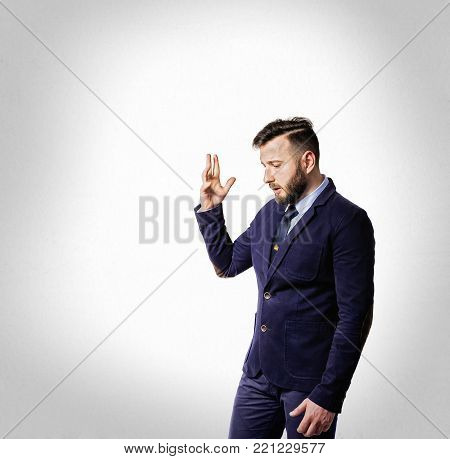 Emotional dialogue of a man in a suit. Portrait of a bearded man on a light background.