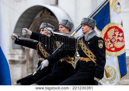 MOSCOW, RUSSIA - DECEMBER 09, 2017: Group of the banner-bearers (color guard) of the Presidential Regiment of the Service of Moscow Kremlin's Commandant of the Federal Guard Service of the Russian Federation. Winter view. Cathedral Square, Kremlin, Moscow