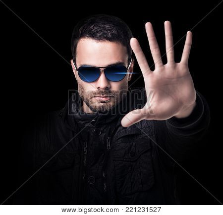 Handsome man in sunglasses shows stop signal. Over black background.