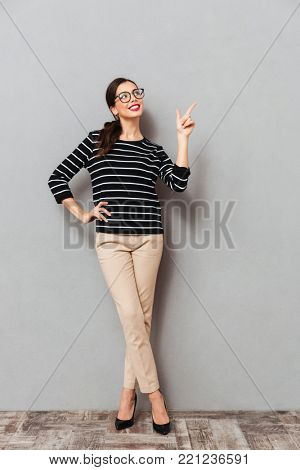 Full length portrait of a smiling businesswoman in eyeglasses standing and pointing finger away at copy space isolated over gray background