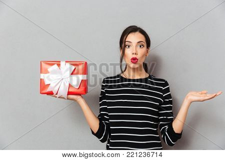 Portrait of a confused woman holding gift box and shrugging shoulders isolated over gray background