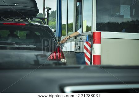 A man pays money to a cashier for a toll road Toll gate motorway entrance