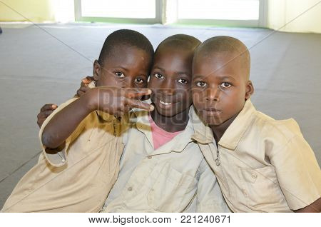 yamoussoukro, ivory coast - Oclober 02, 2015: a group of 3 ivorian kids looking to the camera and smiling. ivory coast yamoussoukro