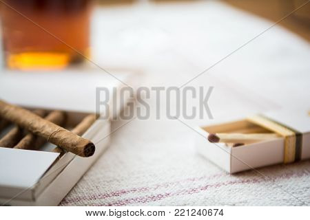 Cigars And Whiskey On A Light Table Cloth, One Cigar Out Of The Packet