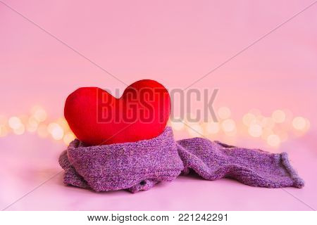 Red soft heart pillow with violet purple warm scarf and blurry warm white yellow light over lovely light pink background with copy space for text decoration or insertion, warm love Valentine's day concept