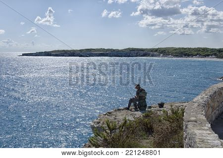 Torre dell'Orso, Italy - September 22, 2017: Solitary angler engaged in bait preparation
