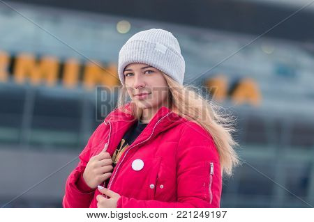 Portrait of a young woman with golden hair, a piercing in her nose, wearing a light grey woven hat and a red coat - winter