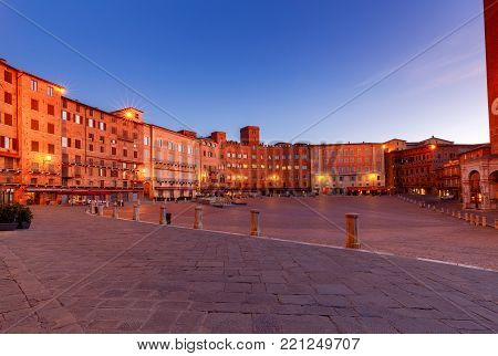 Facades of medieval buildings on Piazza del Campo at night. Siena. Tuscany. Italy. poster