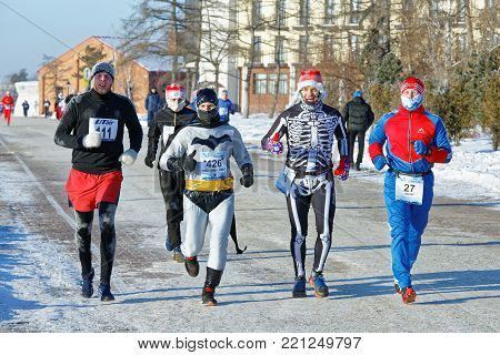 Editorial. Omsk, Russia - January 07 2018. 27th Christmas winter half marathon. Athletes dressed in different costumes run on the Embankment Tukhachevsky Street