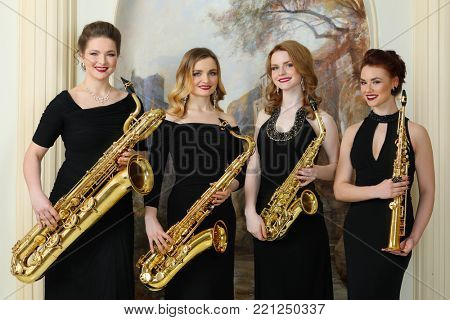 MOSCOW - APR 30, 2017: Four women (with model releases) pose with saxophones in studio Cross photo