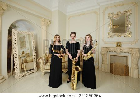 MOSCOW - APR 30, 2017: Three women (with model releases) pose with saxophones in studio Cross photo