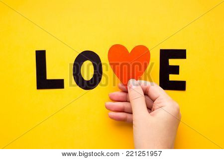 Word LOVE with hand on simple yellow background surface. Letters and heart made of color paper and cardboard. Valentines day concept.
