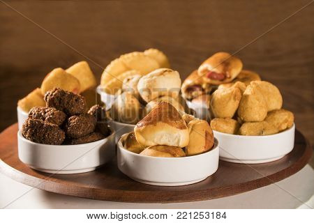 Mixed brazilian snack on wood background. Salgadinhos.