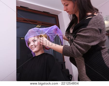 Portrait of happy woman in beauty salon. Blond girl with hair curlers rollers by hairdresser. Hairstyle.