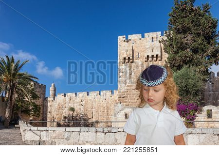 Handsome little boy with blond side curls and blue eyes, in skullcap. Autumn Jewish holiday Sukkot.    Jerusalem, Israel