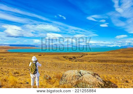 An elderly woman -  photographer with a backpack enthusiastically taking pictures of a Patagonian pampas