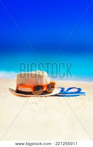 Flip-flops, beach hat, sun glasses on the sand. Summer vacation concept. Summer fun time and accessories on tropical beach