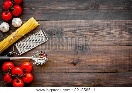 Preparing to cook pasta. Spaghetti, tomatoes, garlic, cheese grater, spoon for spaghetti on dark wooden table top view.