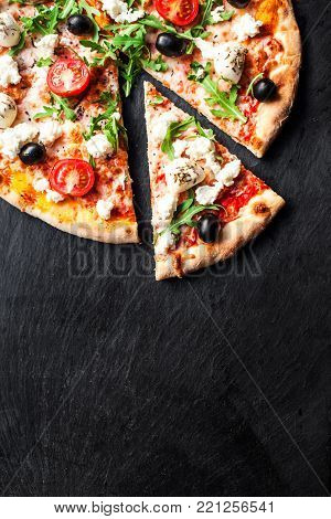 Hot pizza slice with melted mozzarella cheese and tomato on black concrete background.  Pizza Ready to Eat, Copyspace.