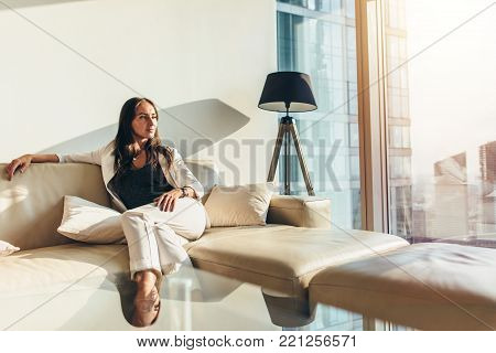 Portrait of successful businesswoman wearing elegant formal suit sitting on leather sofa relaxing after work at home.