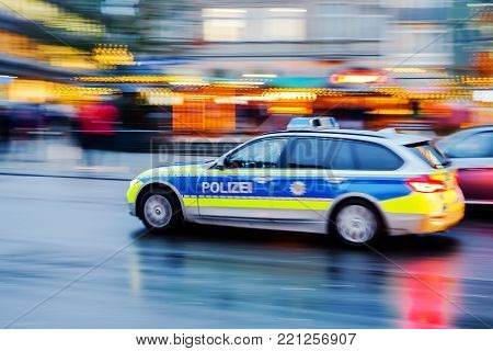 Aachen, Germany - December 21, 2017: North-Rhine Westphalian police car in motion blur at dusk. The NRW Police Force is the biggest of 16 German state police with roughly 50,000 officers