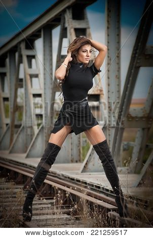 attractive woman with short black dress and long leather boots standing on the rails with bridge in background. Fashion  sexy girl , on the bridge posing in  black long boots on high heels