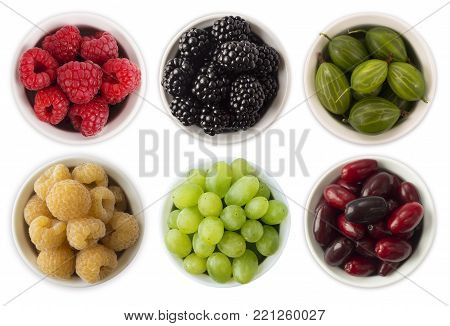 Fruits and berries in bowl isolated on white. Sweet and juicy berry with copy space for text. Rasberries, blackberries, gooseberries and grapes. Collage of different fruits and berries. Berry on a white background. Top view. Various fresh summer.