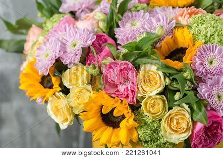 beautiful bouquet of mixed flowers in a vase on wooden table. the work of the florist at a flower shop. a bright mix of sunflowers, chrysanthemums and roses.