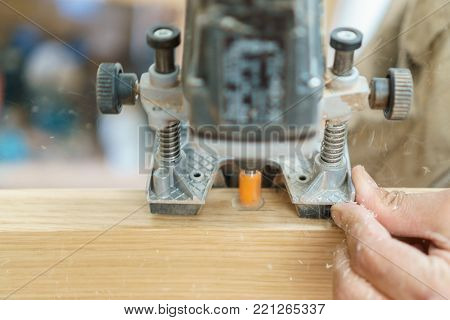 Carpenter hand working over door edge creating hinges holes with specific machine