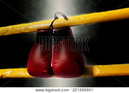 Pair of red boxing gloves hangs off the boxing ring. Soft focus