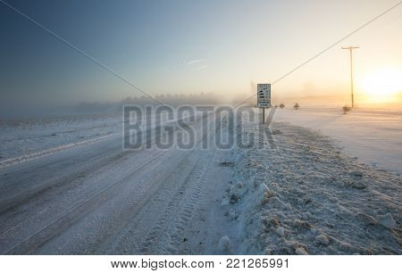 Winter Driving Background. Rural country snow covered road with a frigid winter wind blowing snow across the horizon.