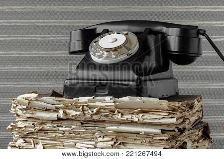 Old black telephone is on the book with tattered pages