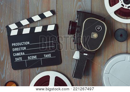 The clapper board, the old movie camera and the coils with the films lie on a wooden table. The view from above.