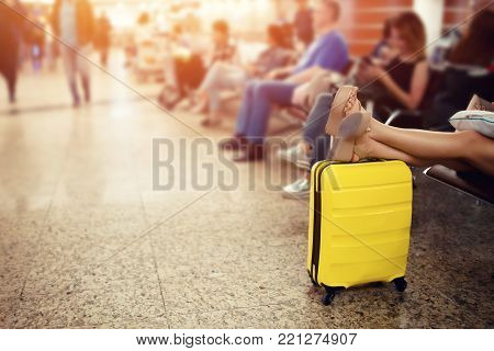 Passenger girl with carry on luggage waiting for delay flight in airport terminal and relaxing time.