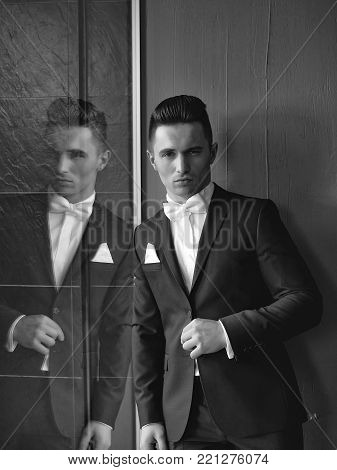 Man in suit with white handkerchief and bow tie young elegant stylish stands with serious look and reflects in mirror on grey background