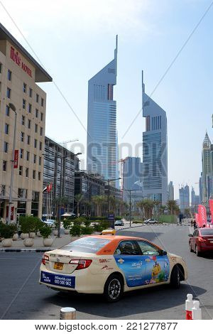 DUBAI, UAE - NOVEMBER 17: The Emirates Towers, and Taxi car on November 17, 2017. The Emirates Towers complex is set in over 570,000 m2