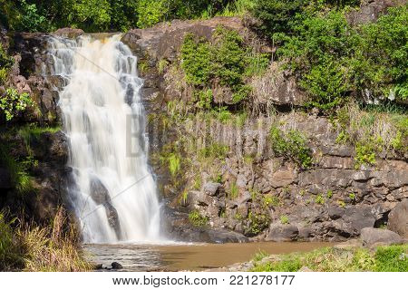 Scenic view of the Waimea Falls, North Shore, Hawaii cascading over a rocky cliff into a quiet pool below