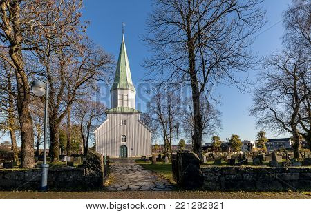 White wooden church, trees and blue sky in autumn, Oddernes Church is the oldest building in Kristiansand, buildt around 1040. Kristiansand, Norway