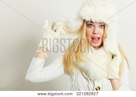Winter fashion. Young blonde woman wearing fashionable wintertime clothes white fur scarf cap, woolen gloves, studio shot