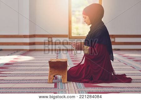 Young muslim woman with hijab praying in mosque.