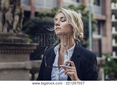Portrait of relaxed woman with her eyes closed in classic suit holding eyeglasses, enjoying the moment, breathing