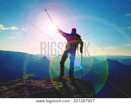 Hiker with  medicine crutch above head achieved  personal target. Broken leg fixed in immobilizer Deep misty valley bellow silhouette of man with hand in air. Spring daybreak