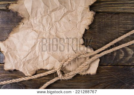 Part of the old burnt parchment and a knot of hemp rope lying on the Old wooden table. A place for your inscriptions