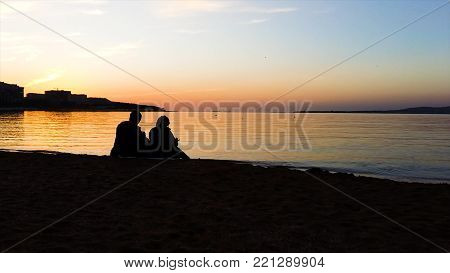 Silhouette of man and woman watching the sunset. Silhouette of the couple enjoying the sunset on the beach. Young couple sitting on a bench at sunset. There is a flying bird, silhouette