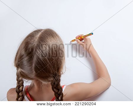 The girl with pigtails photographed from the back and from the top point drawing with a colorful pencil on a white background